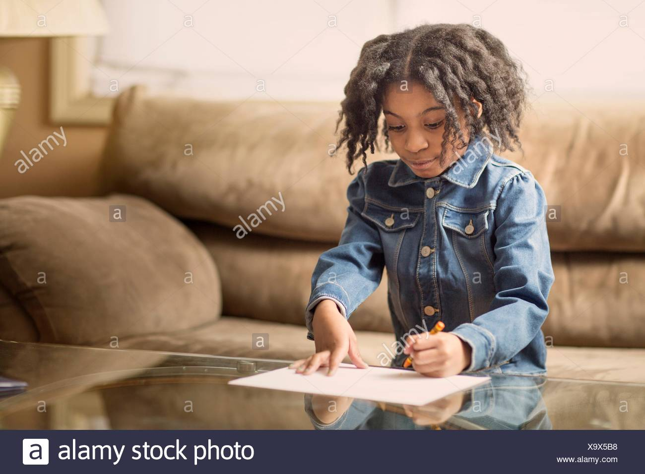 Girl drawing on coffee table - Stock Image