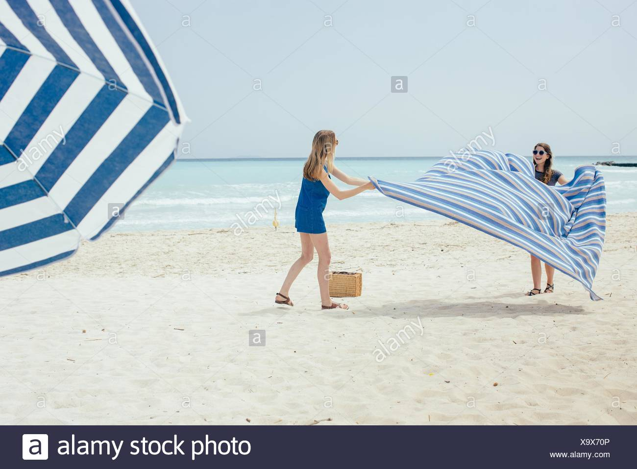 Two young female friends laying out picnic blanket on beach - Stock Image