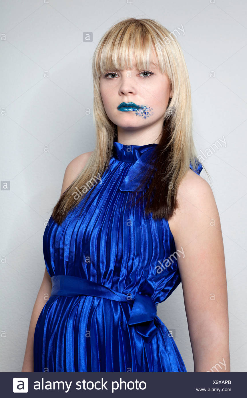 Young blond woman wearing a blue dress and blue lipstick Stock Photo