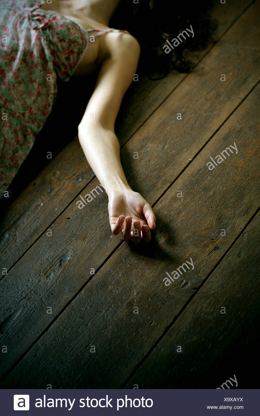 dead woman lying on the floor, focus on the hand - Stock Image