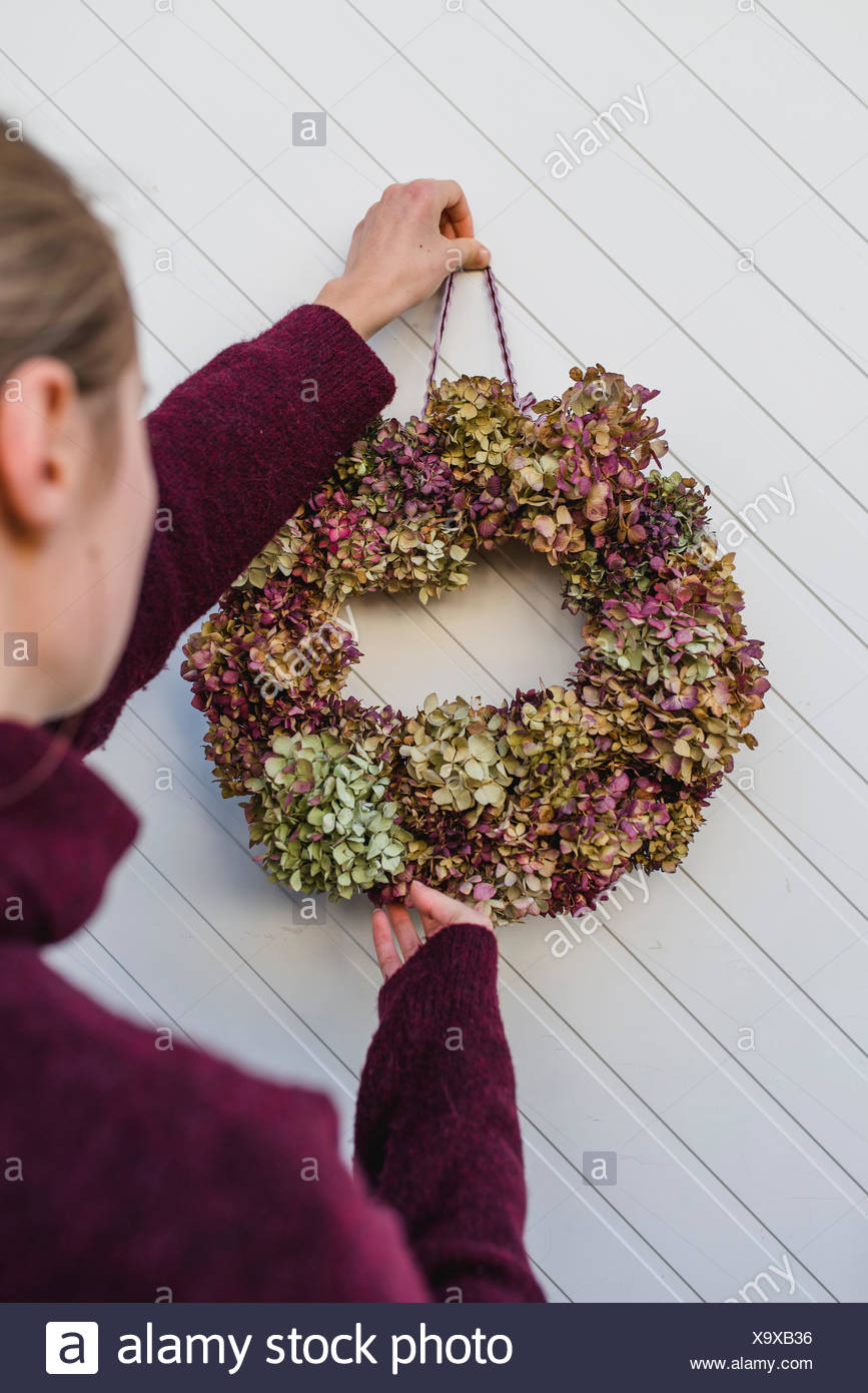 Woman, detail, autumnal decoration, wreath with hydrangea blossoms, door, hang up, - Stock Image