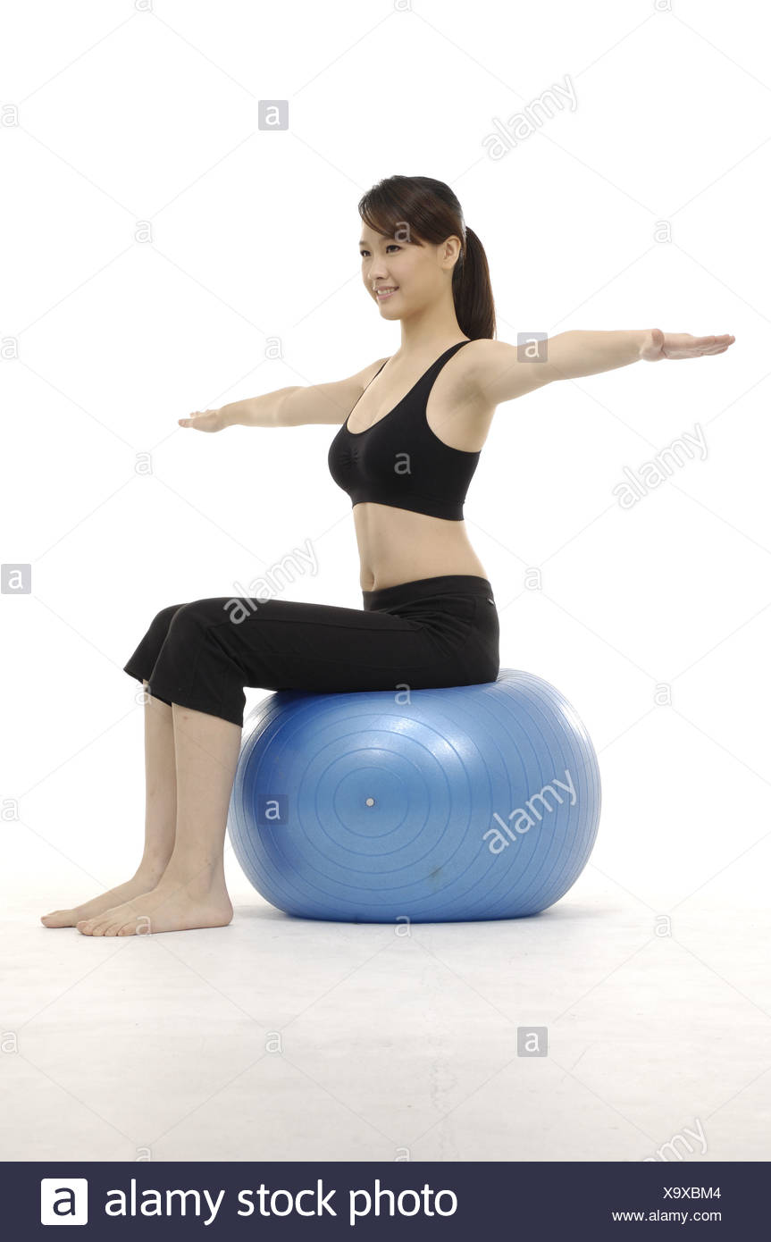 young woman practicing yoga on exercise ball - Stock Image