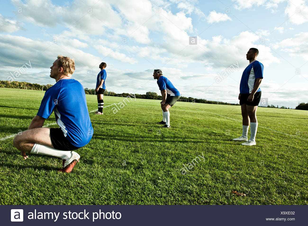 Soccer players standing on pitch - Stock Image