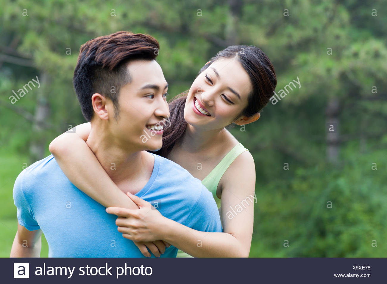 Young man giving her girlfriend a piggy back ride - Stock Image