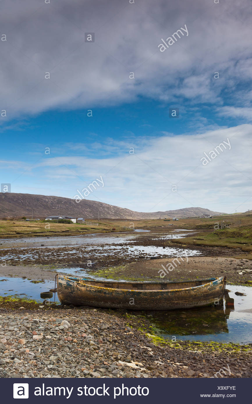 An Old Abandoned Rowboat In The Shallow Water; Shetland Scotland - Stock Image
