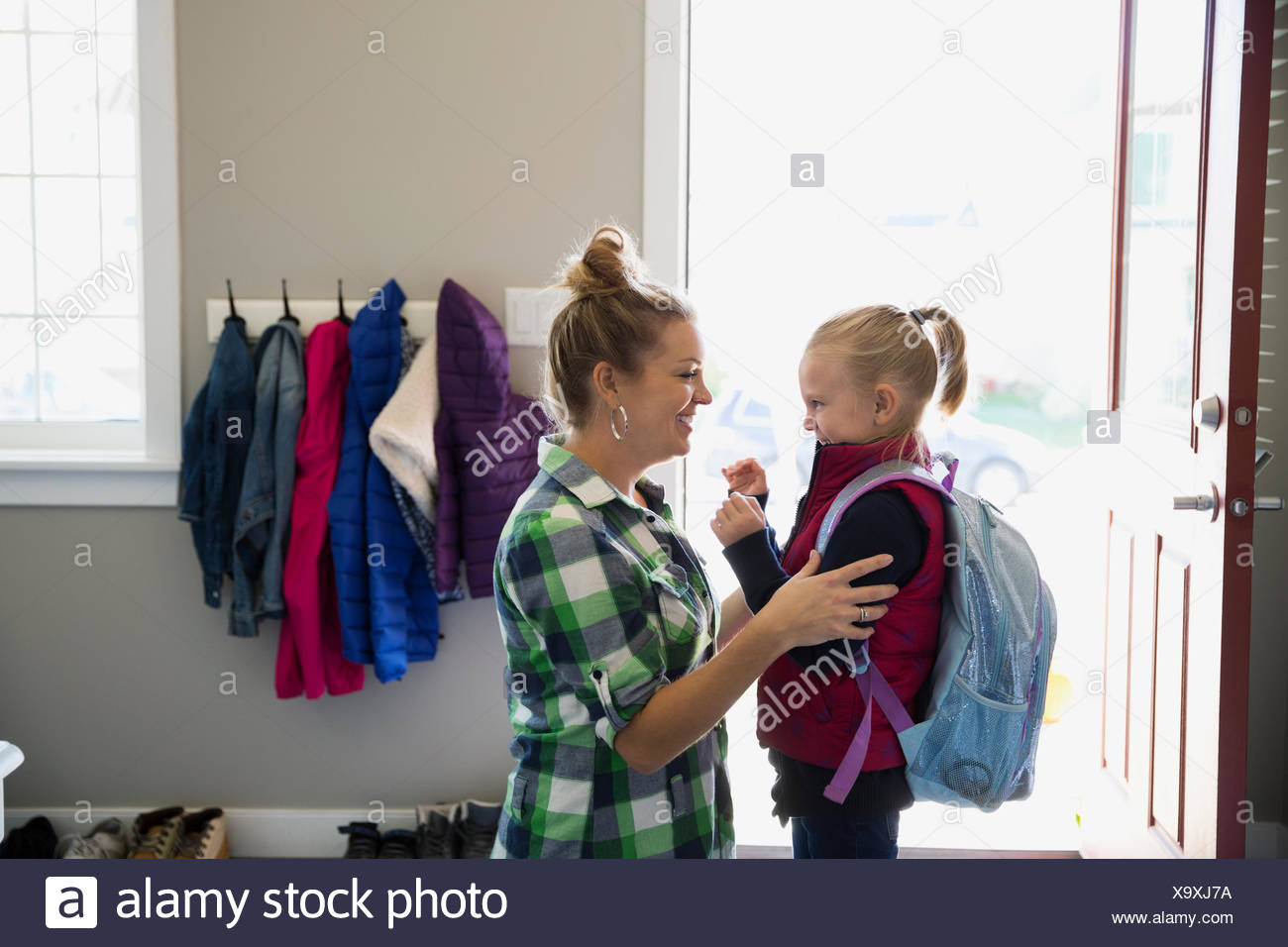 Mother saying goodbye to daughter with backpack - Stock Image