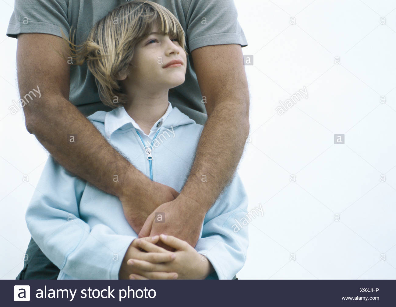 Boy standing with father's arms around him - Stock Image