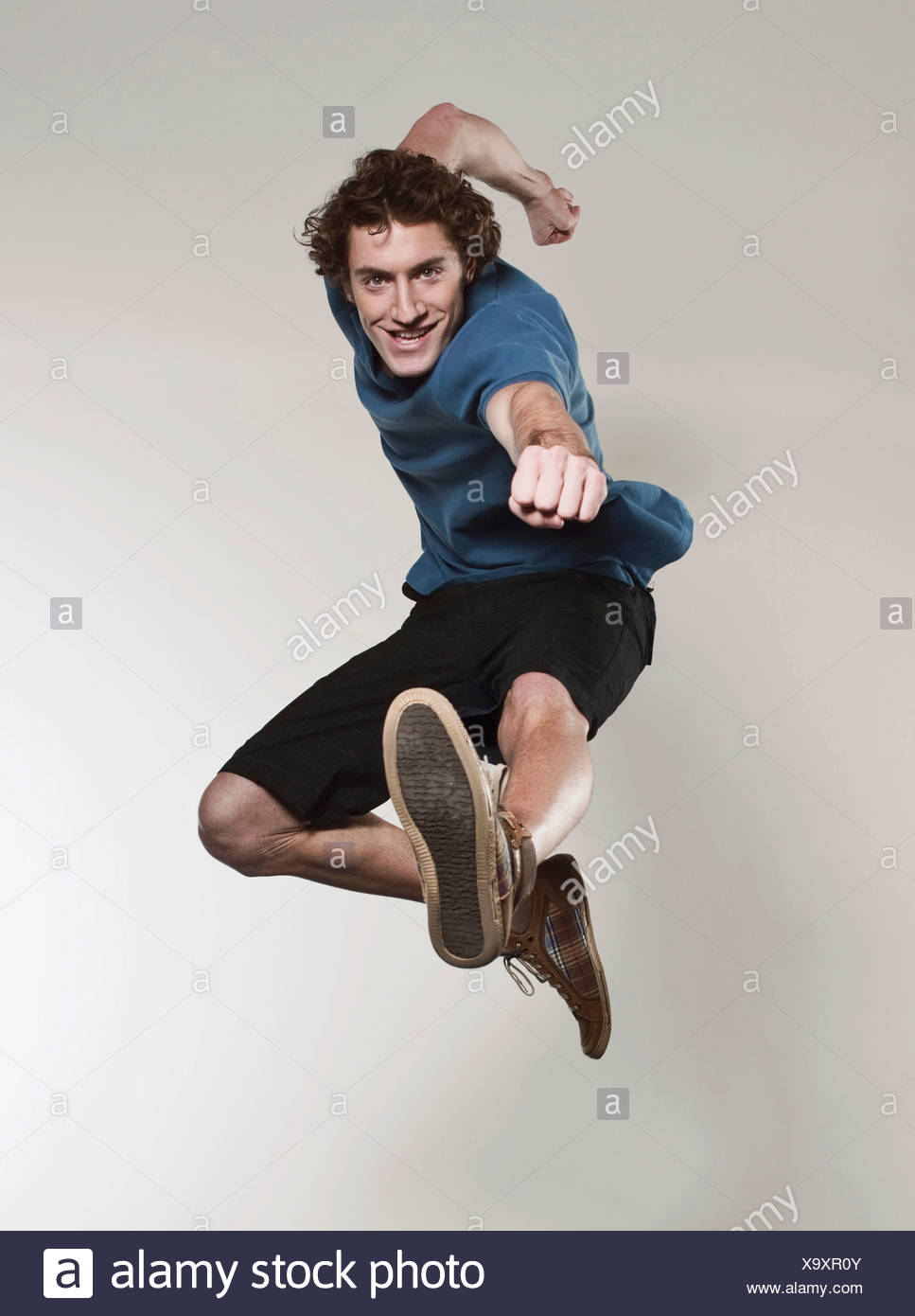 Man jumping and punching in air, smiling, portrait - Stock Image