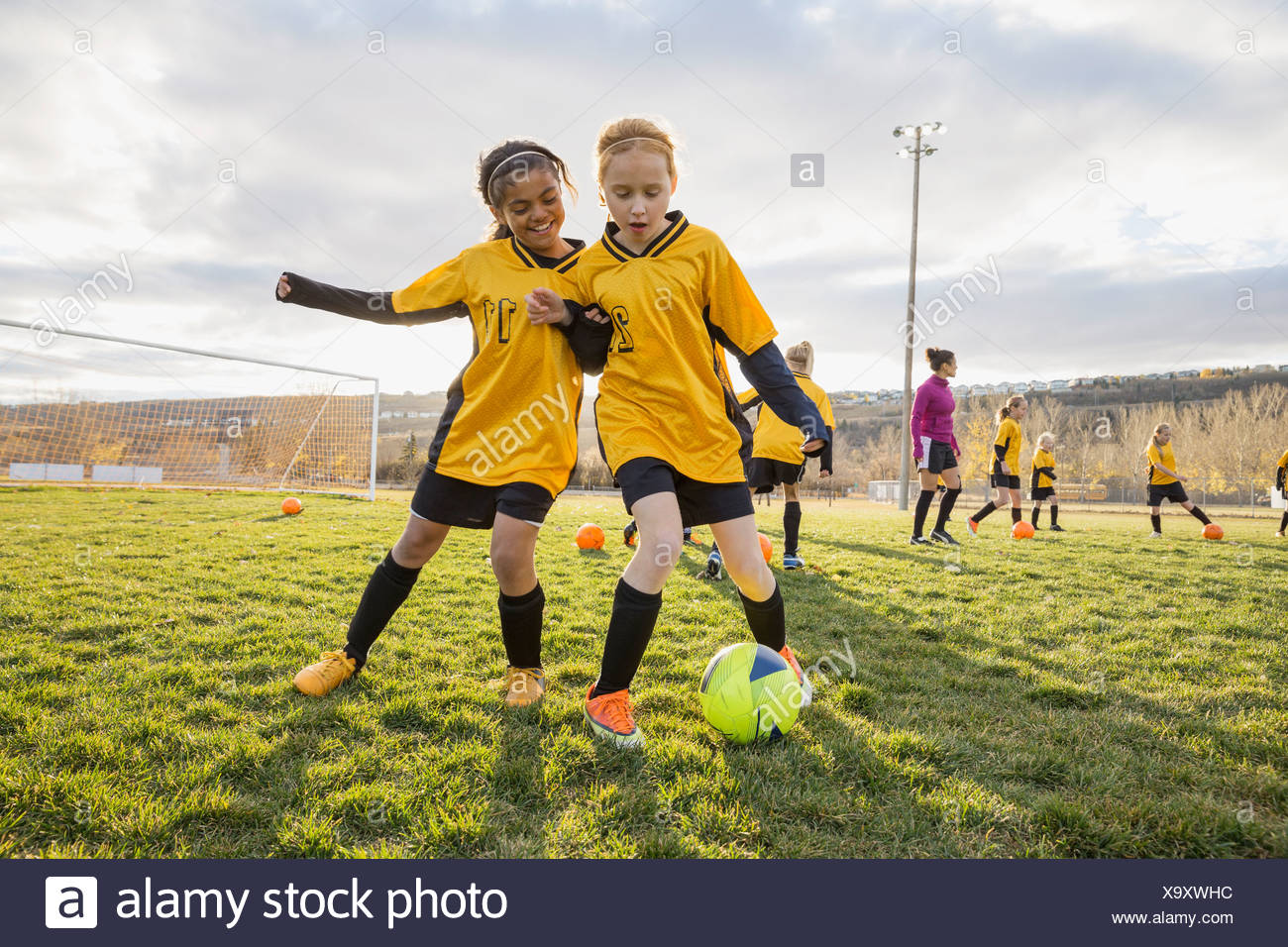 Girls practicing soccer drills on field - Stock Image