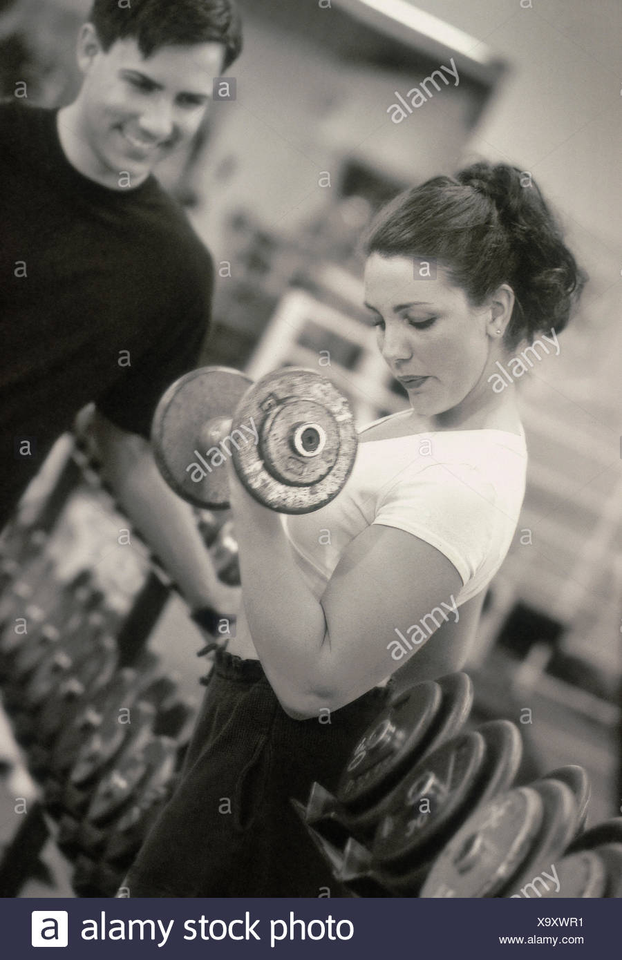 Caucasian female and male lifting weights in fitness club (Model Released) - Stock Image