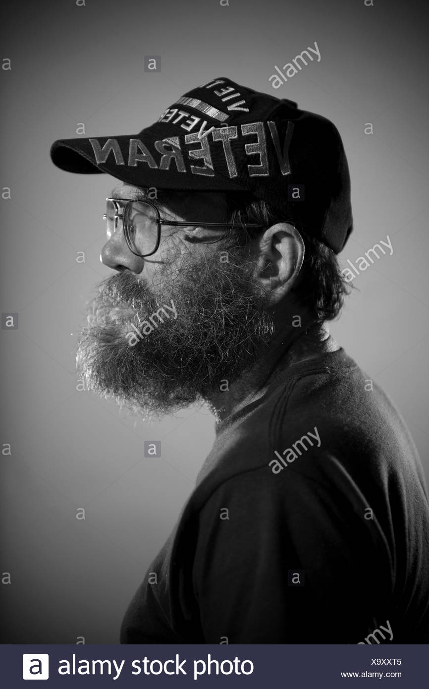 A male veteran wears a war related ball cap with thick glasses and a full beard. - Stock Image
