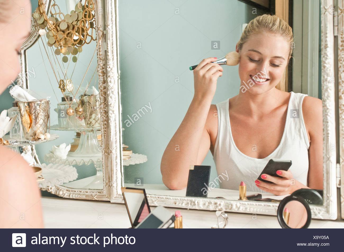 Woman applying make up - Stock Image