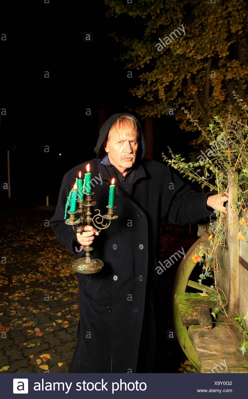 monk with candle holders - Stock Image