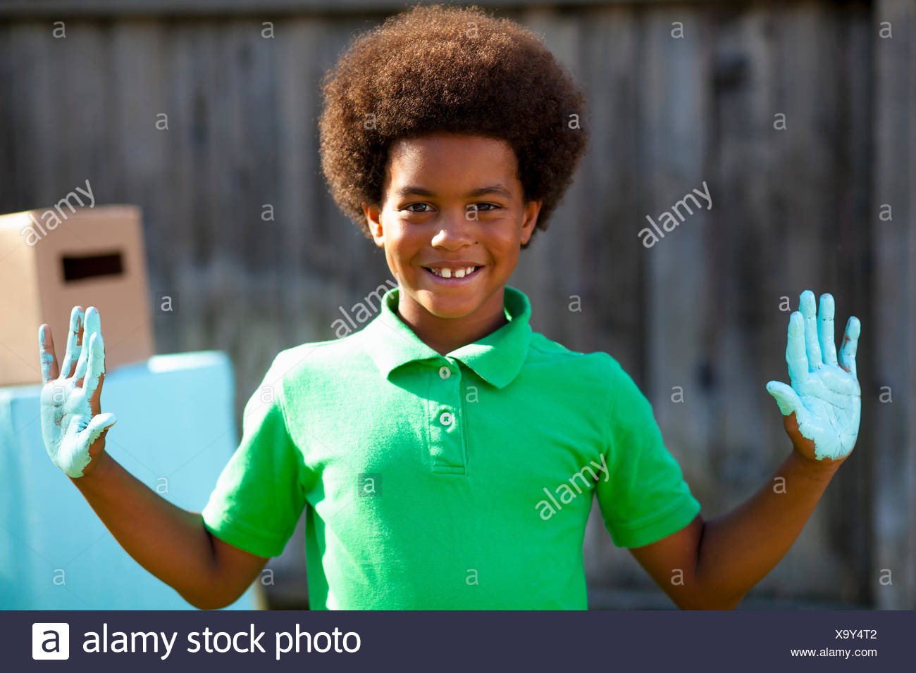 Portrait of boy with blue painted palms in front of home made robot - Stock Image
