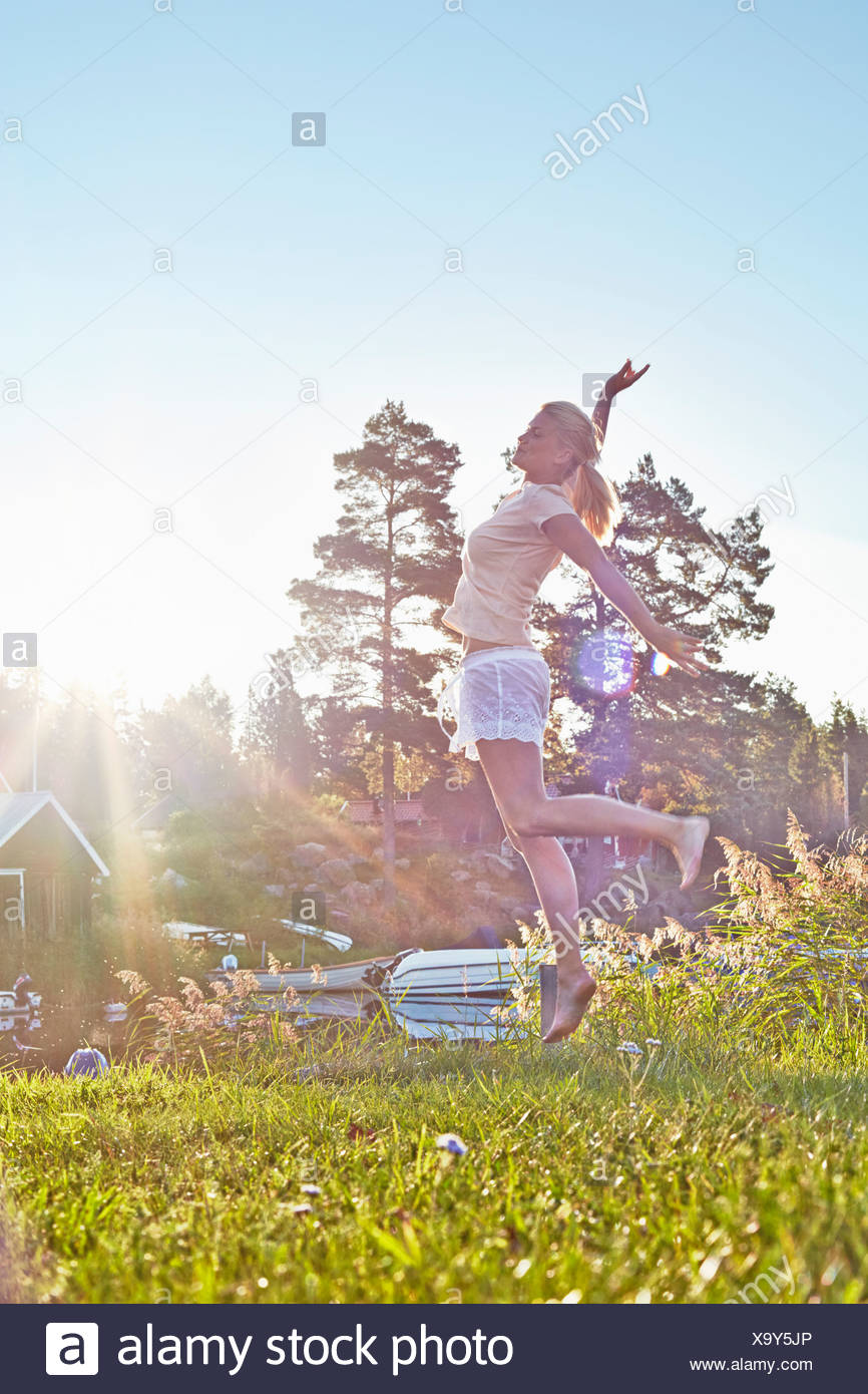 Young woman leaping next to lake, Gavle, Sweden - Stock Image