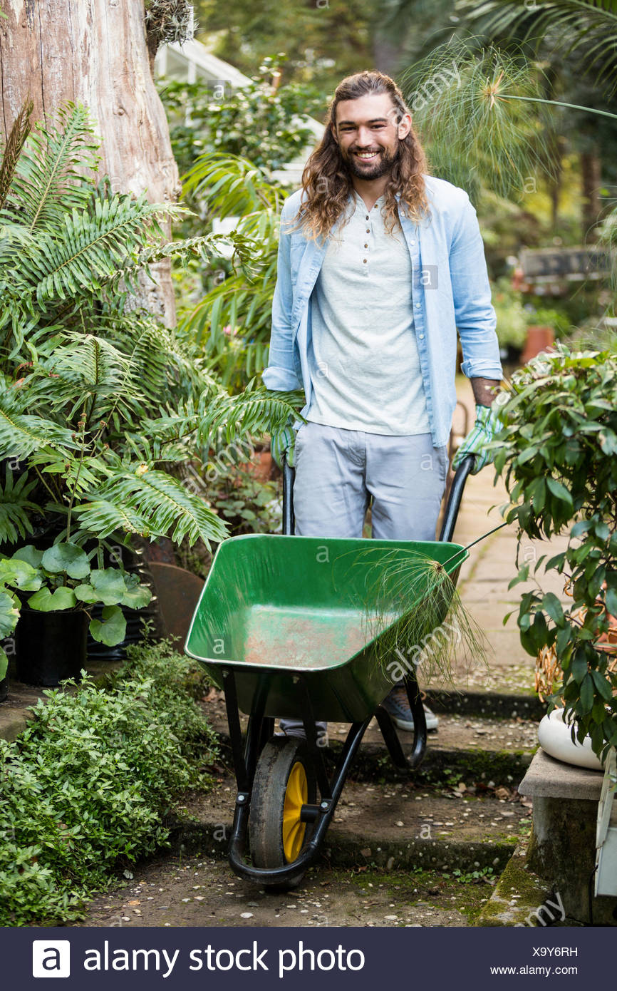 Portrait of happy gardener pushing wheelbarrow at garden - Stock Image