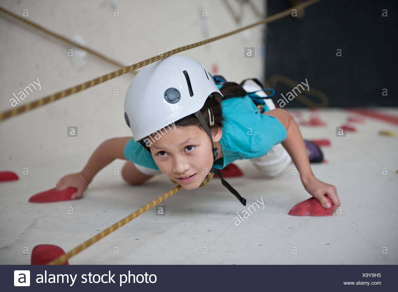 Girl climbing with ropes on climbing wall - Stock Image