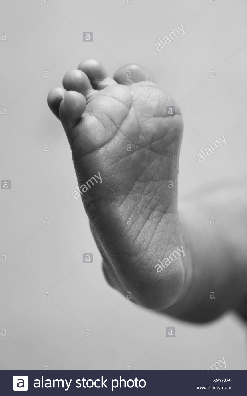 Cute baby infant wrinkled foot sole with toes in black and white, grayscale. - Stock Image