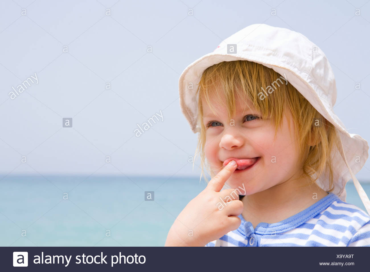 Portrait of baby at beach with tongue out - Stock Image