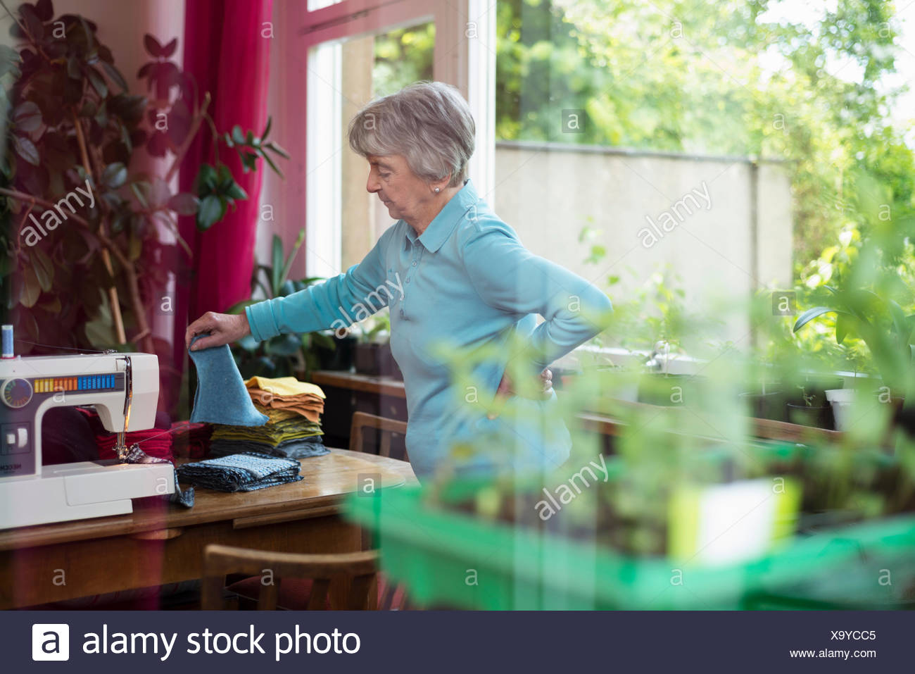 Senior woman choosing fabric by sewing machine - Stock Image