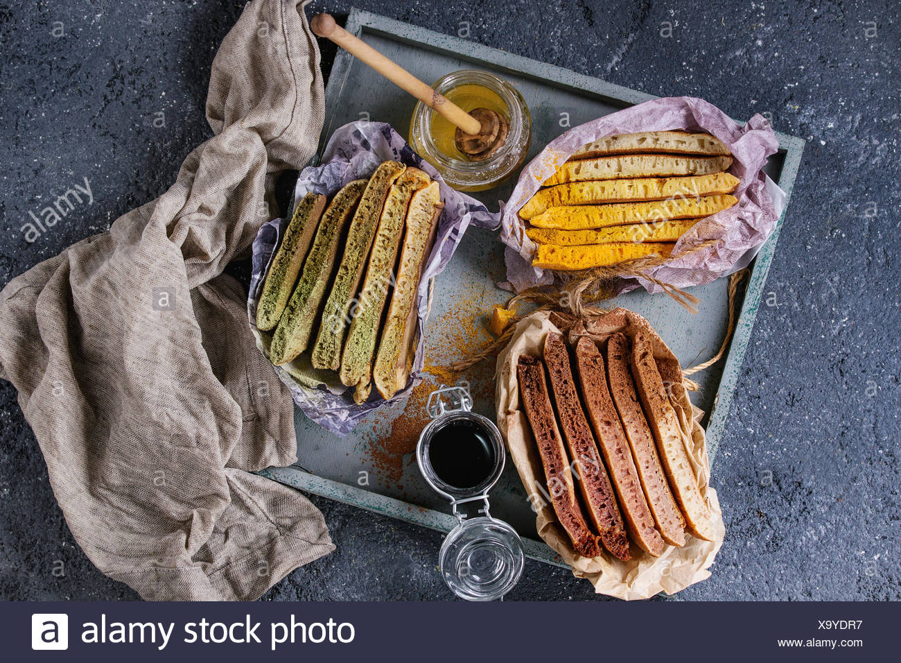 Variety of sliced american ombre chocolate, green tea matcha and turmeric pancakes served in paper paper wrapper with honey sauces on wood tray over b - Stock Image