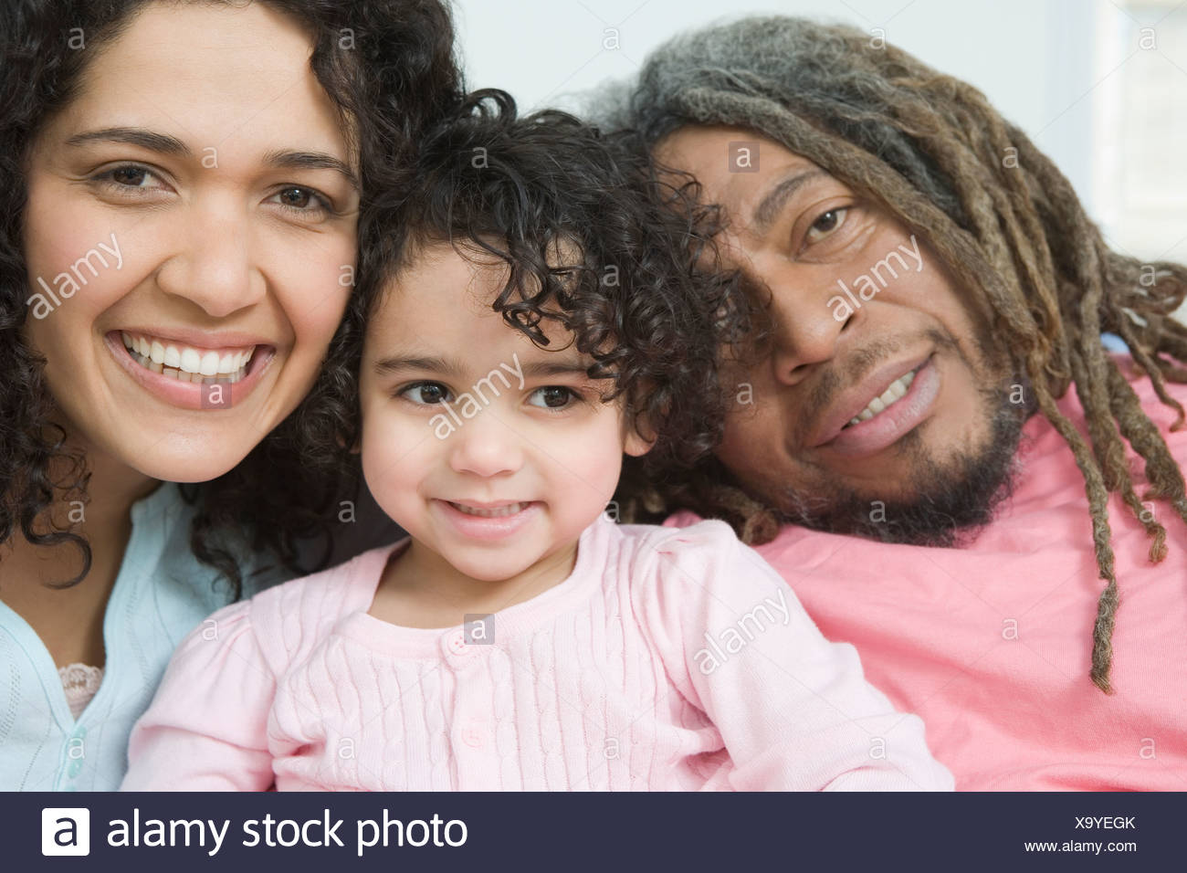 Portrait of a mid adult couple smiling with their daughter - Stock Image