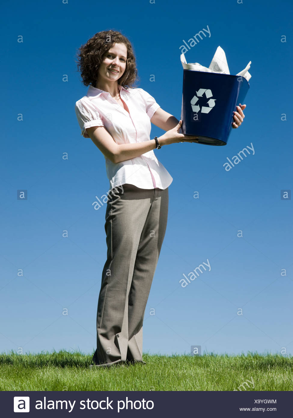 businesswoman holding a recycling bin - Stock Image