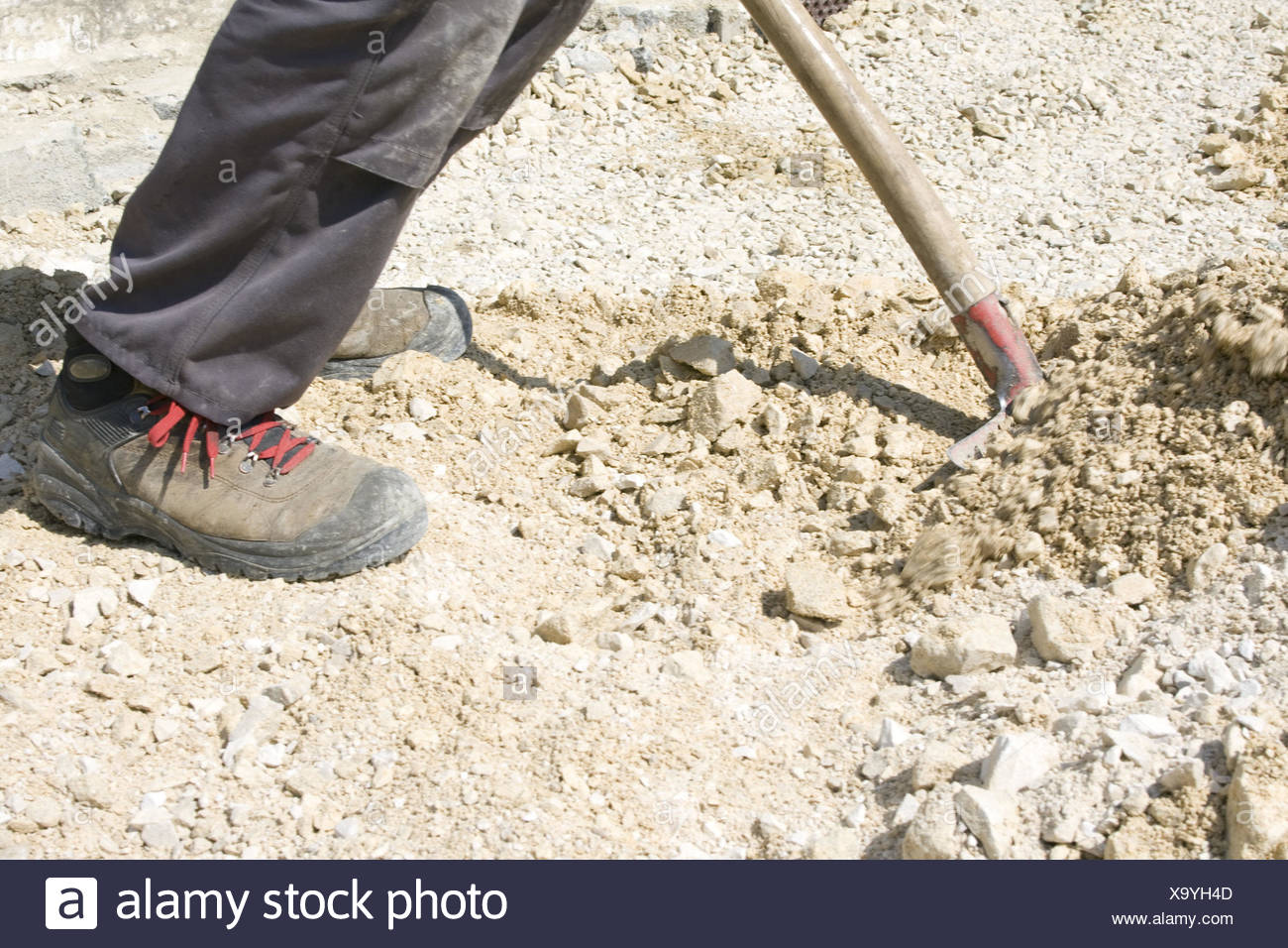 Craftsmen, shovel, gravel, grit, construction, man, men at work, worker, work, shovel shoes, detail, feet, working shoes, working trousers, dirtily, stony, gravel, stone, stones, strain, with difficulty, strenuous, outside, medium close-up, detail, - Stock Image