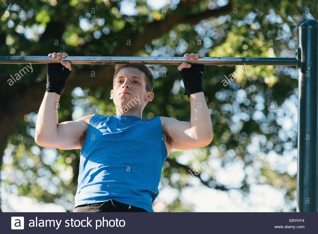 Young man exercising, doing pull-ups on bar - Stock Image