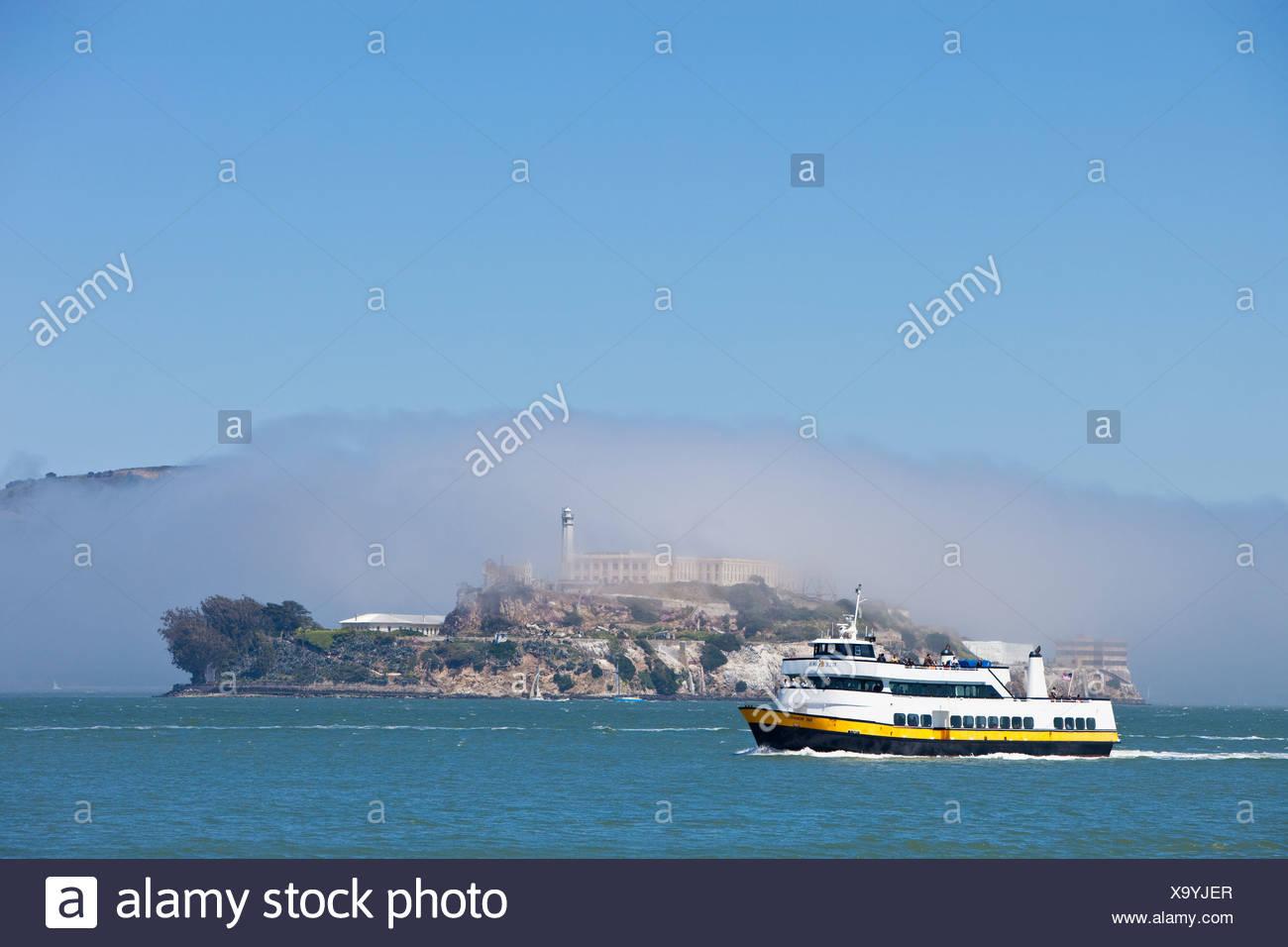 Excursion boat with Alcatraz and fog, former prison island, San Francisco, California, USA, America - Stock Image