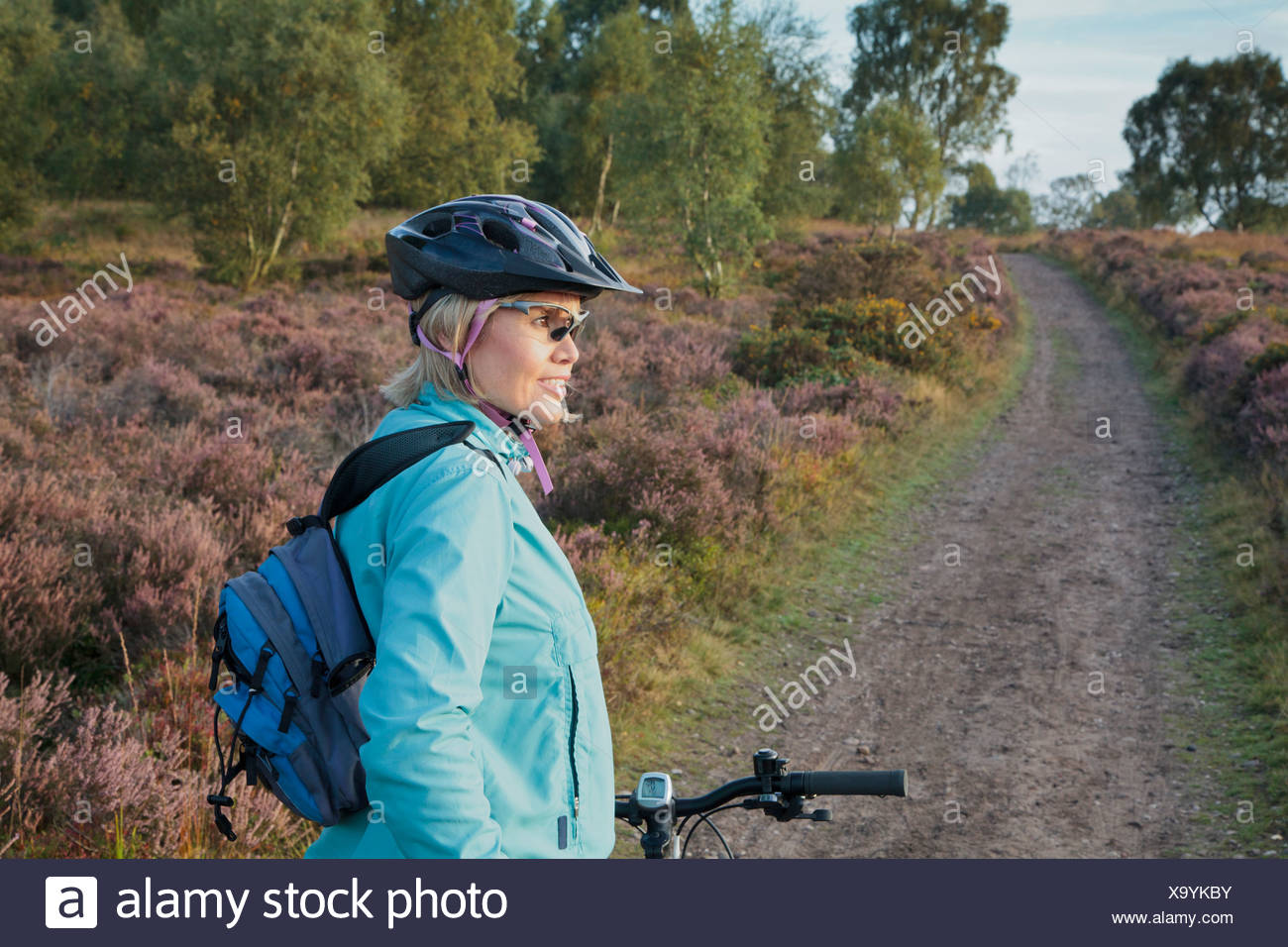 Woman mountain biking on dirt path - Stock Image