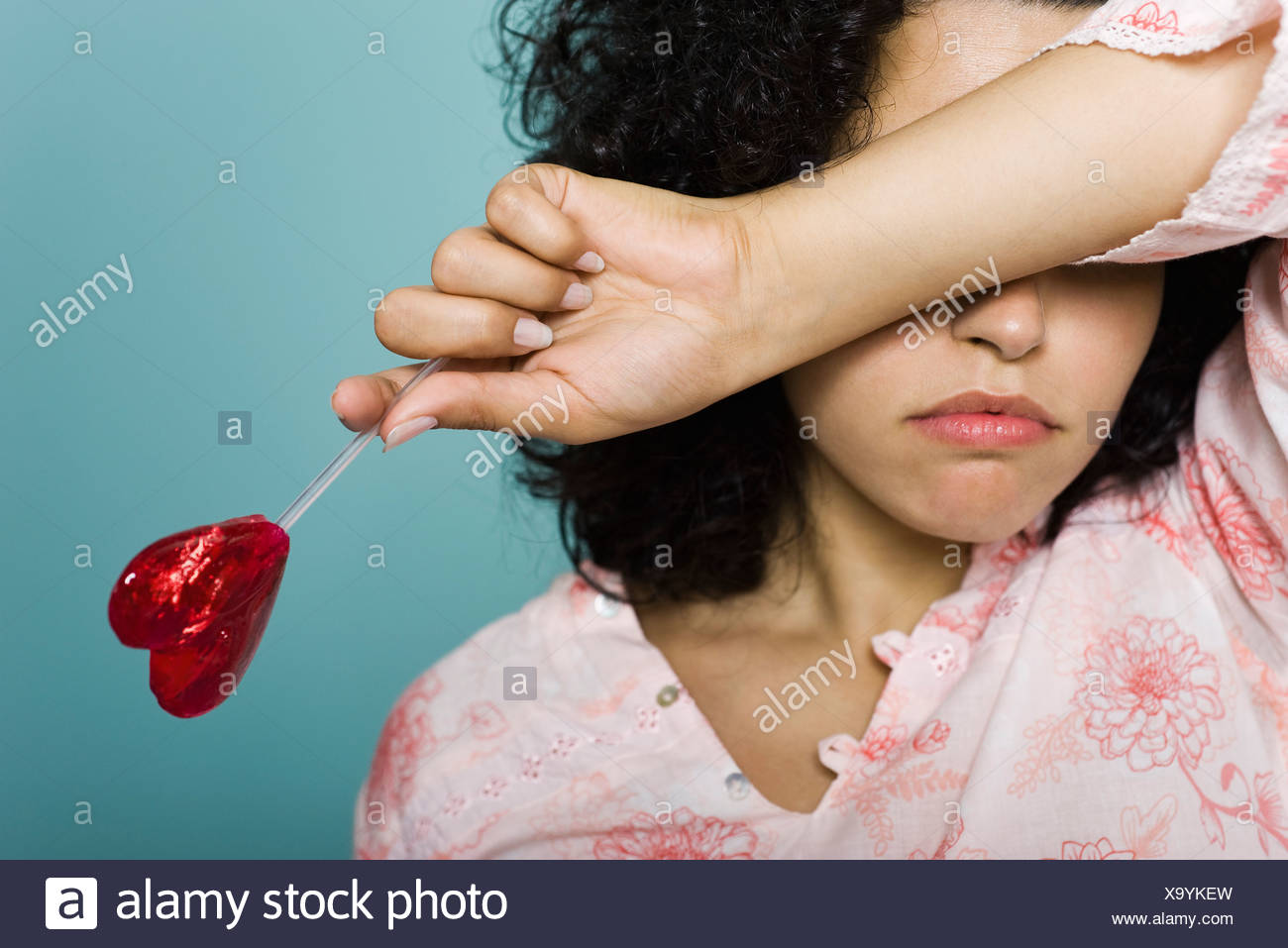 Woman frowning and covering eyes with arm, holding heart-shaped lollipop - Stock Image