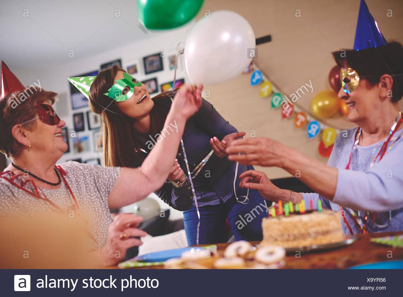 Senior women waving balloons at birthday party - Stock Image