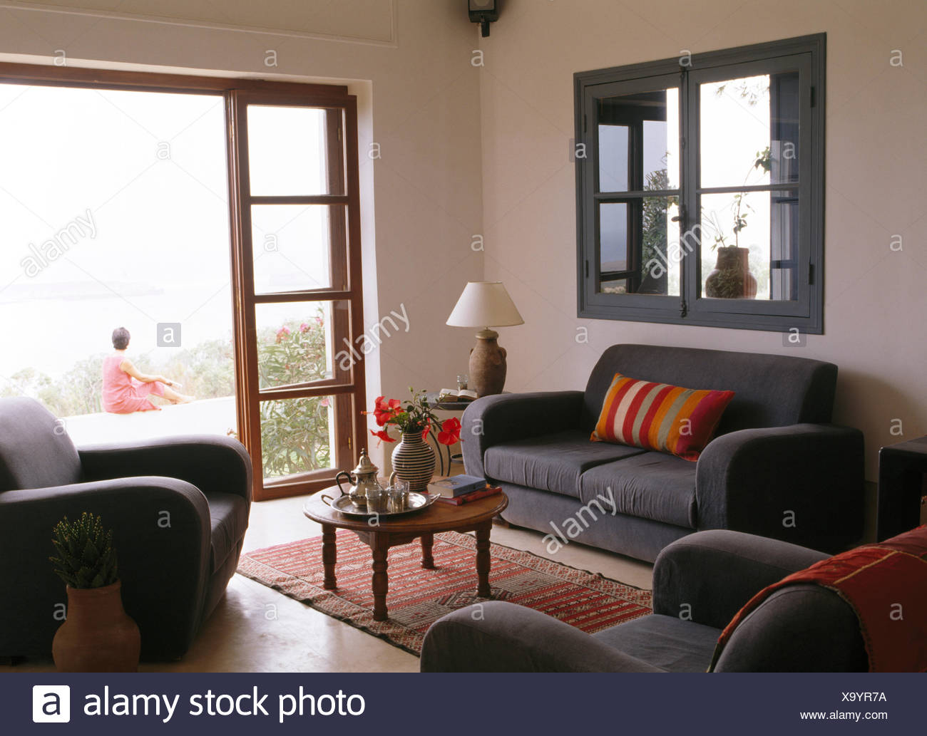 Grey Sofa Below Internal Window In Moroccan Sitting Room With View Through Glass Doors Of Woman Sitting On Patio Stock Photo Alamy