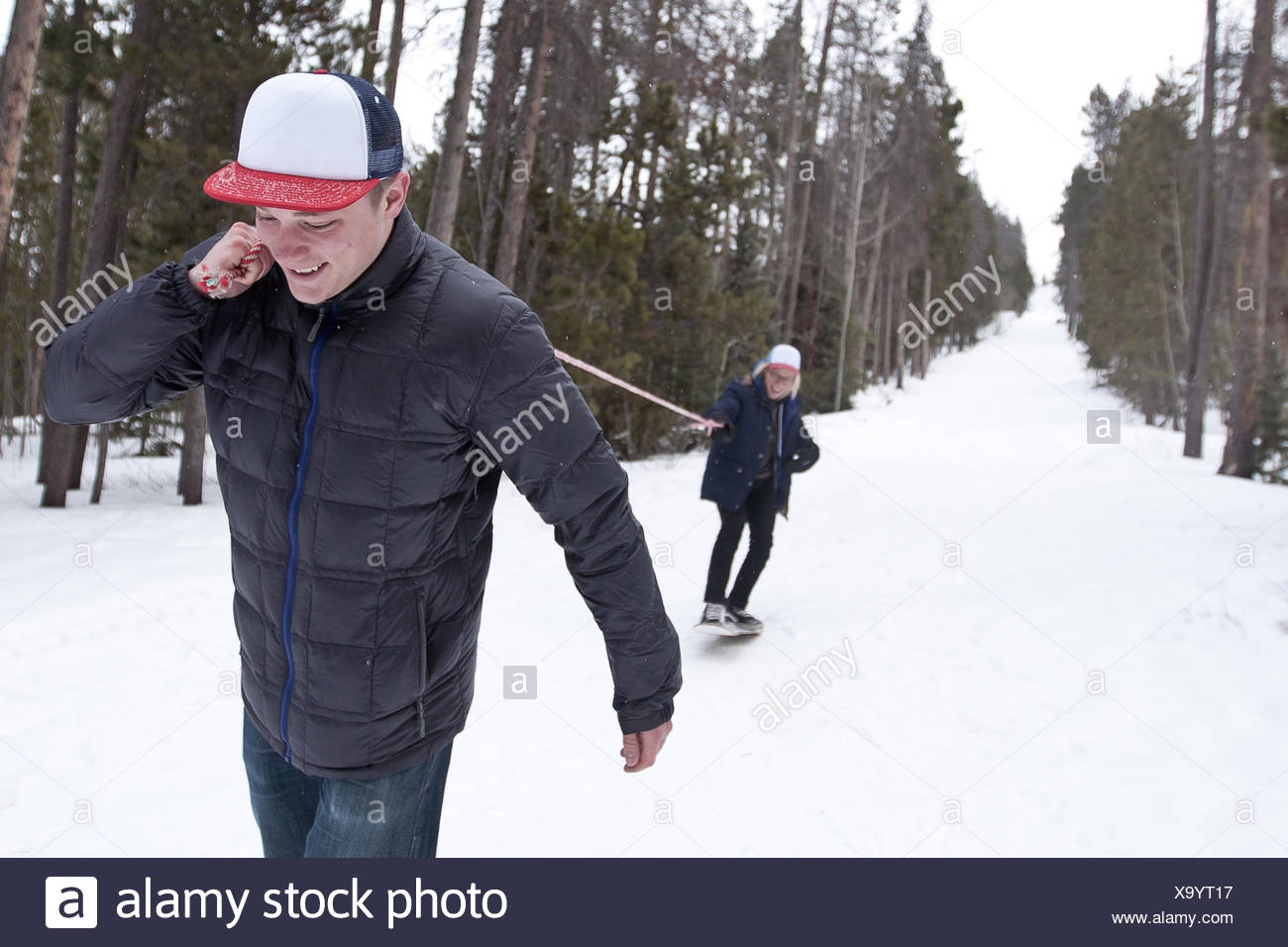 Young man pulling man on snowboard with rope - Stock Image