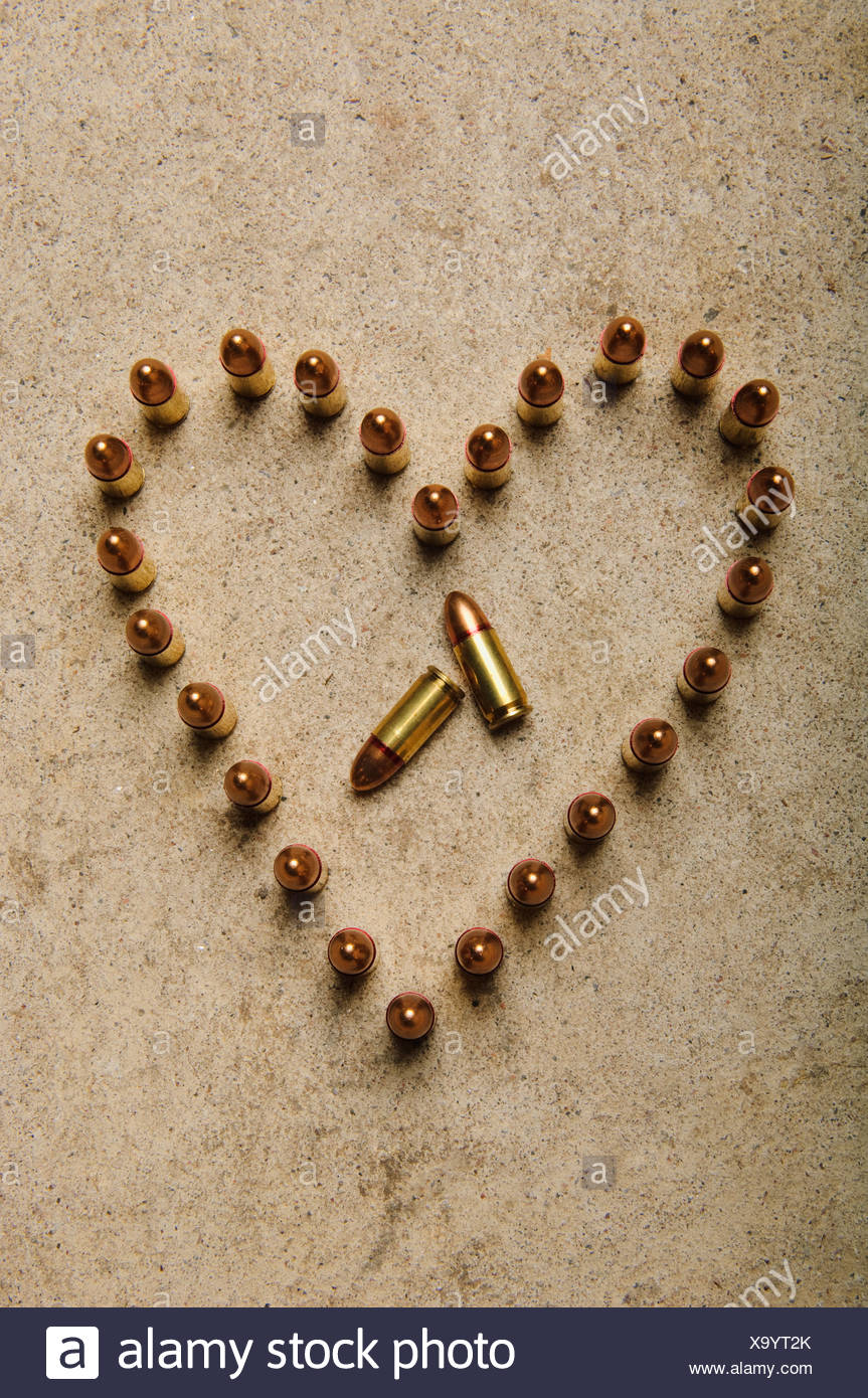 Ammunition on the floor formed into a heart. - Stock Image