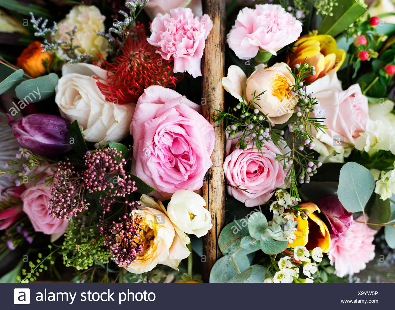 Closeup Of Variety Beautiful Flowers In Wooden Basket Stock Photo