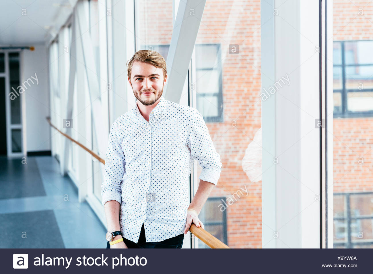 Portrait of confident media student standing at passage in university - Stock Image