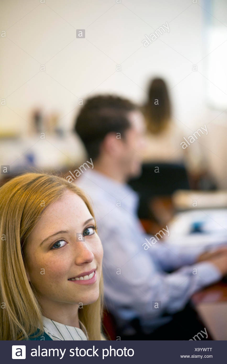Woman working in office, smiling - Stock Image