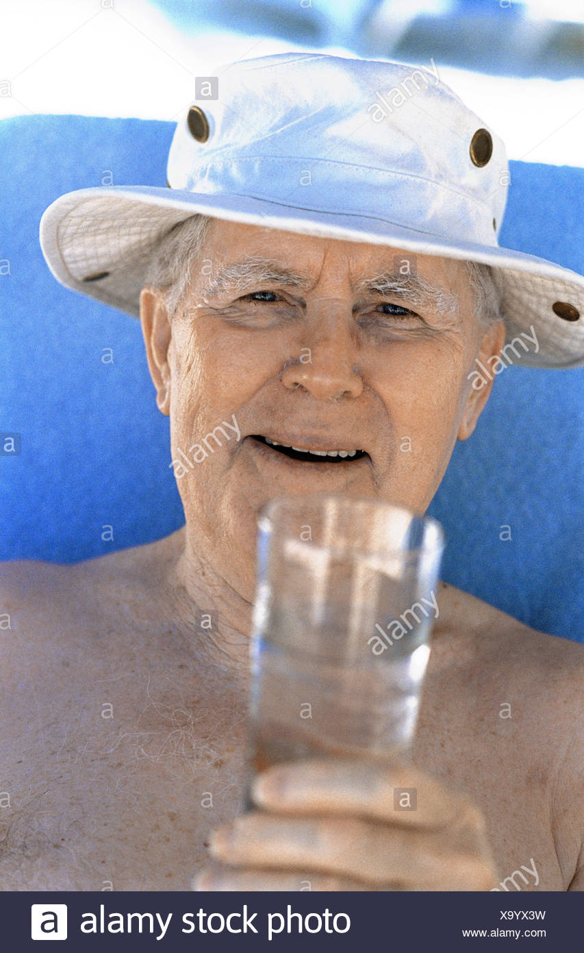 Senior, free upper part of the body, care, water glass, happy, lighthearted, portrait, senior citizens, pensioners, 80 years, retirement age, vacation, summer, refreshment, drink, glass, water, laugh, enjoy view camera, fun, amusement, joy, humor, funnily, vitality, liveliness, fit, agile, actively, young remaining, lighthearted, luck, old age, - Stock Image