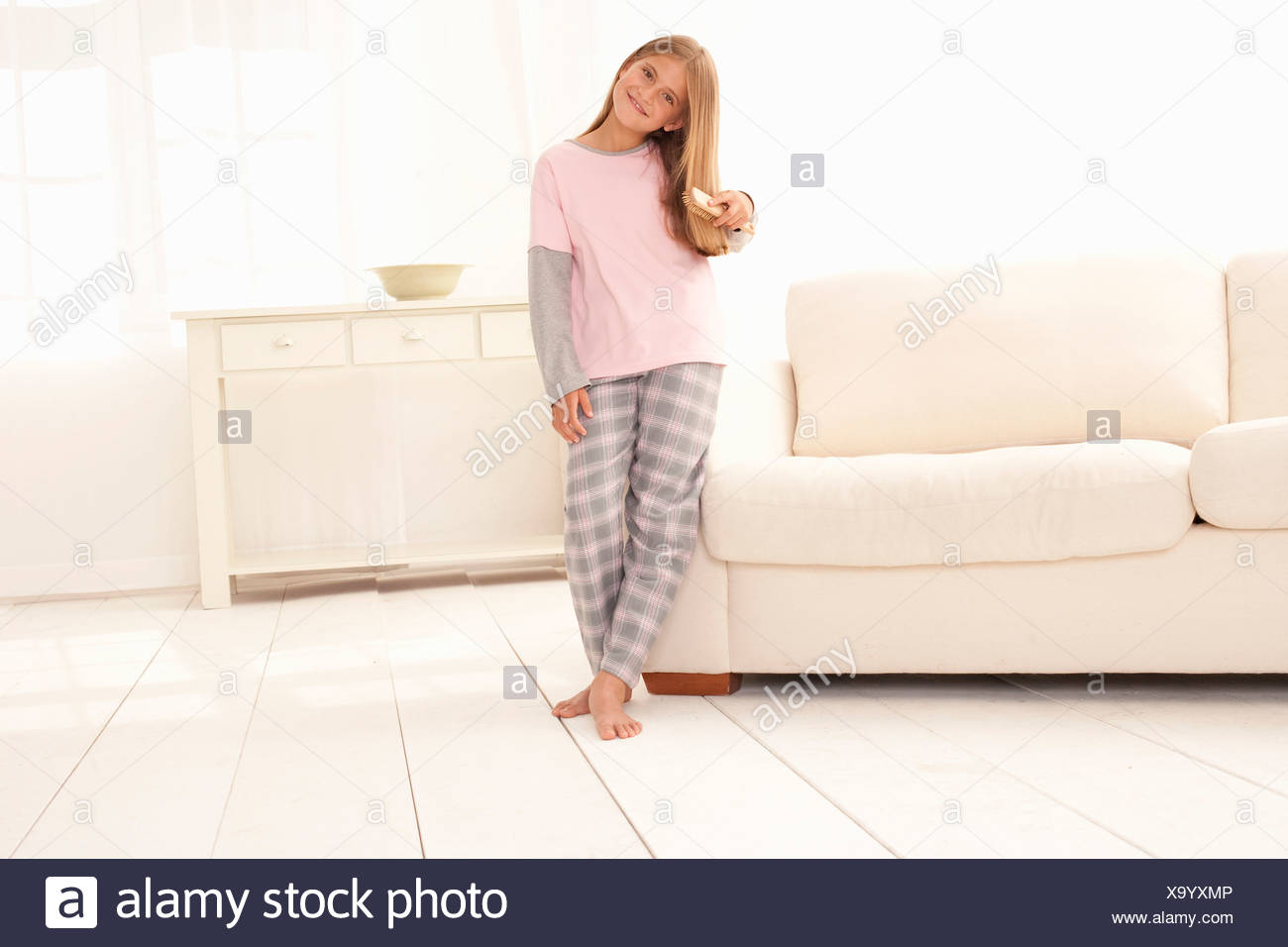 Girl in pajamas leaning on couch - Stock Image