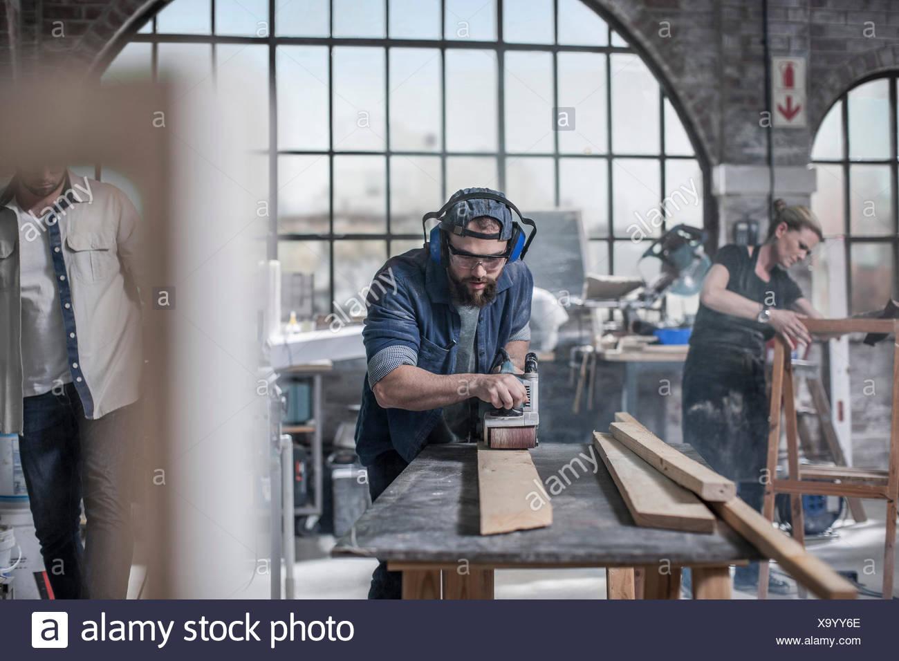 Carpenter sanding wood in antique restoration workshop Stock Photo