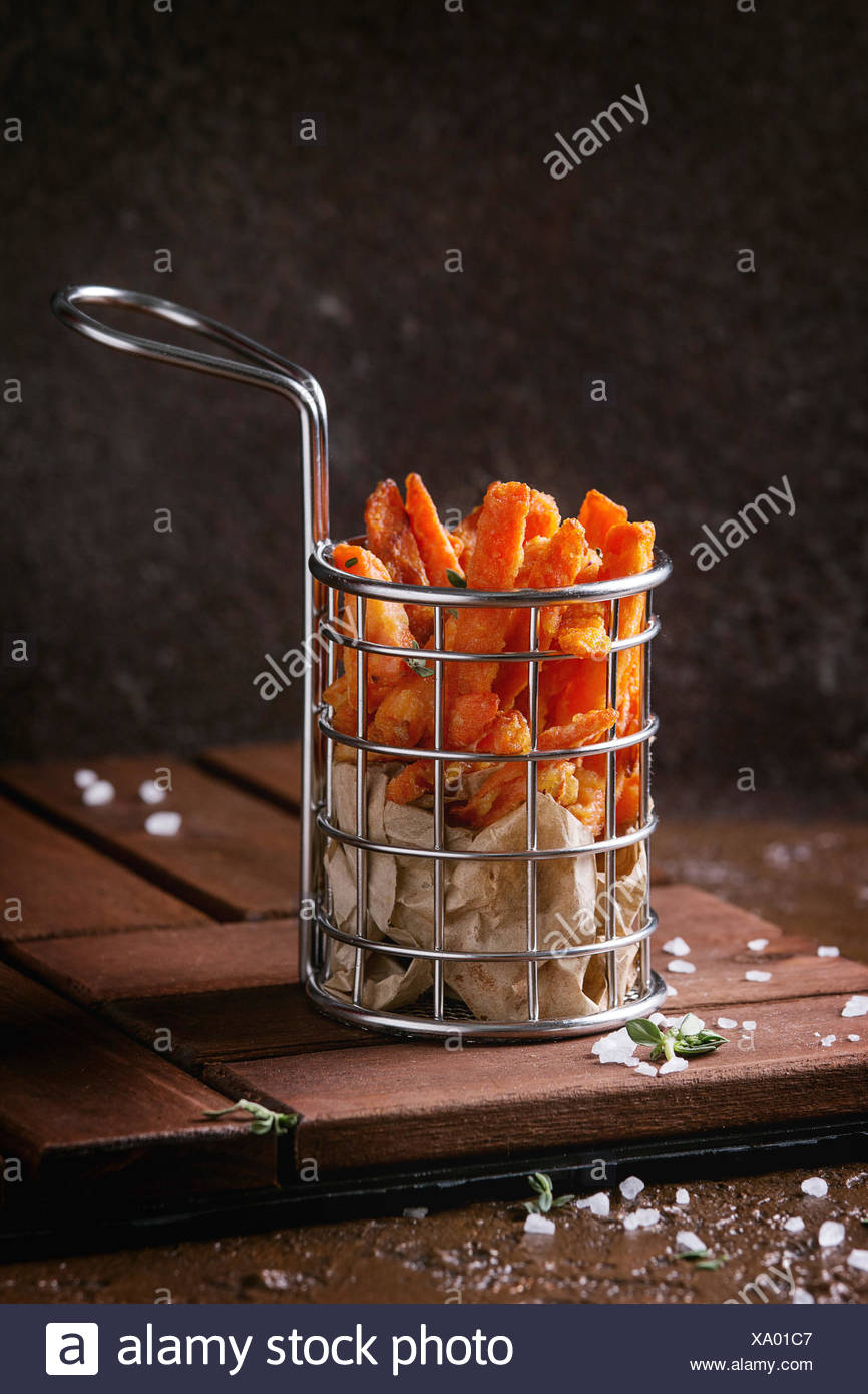 Seet potato or carrot french fries served in frying basket with salt, thyme on wooden board over brown texture background. Homemade fast food - Stock Image