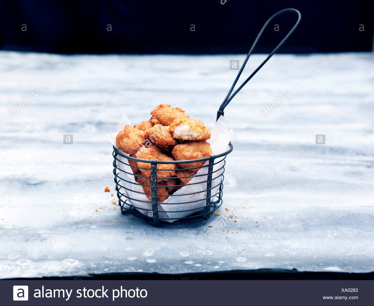 Frying basket full of breaded Scottish wholetail scampi Stock Photo