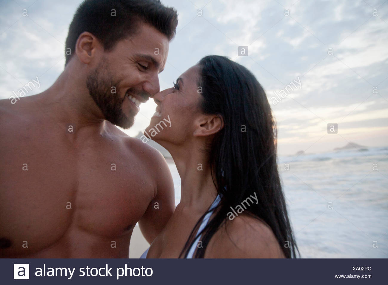 Mid adult couple standing on beach, face to face, touching noses - Stock Image