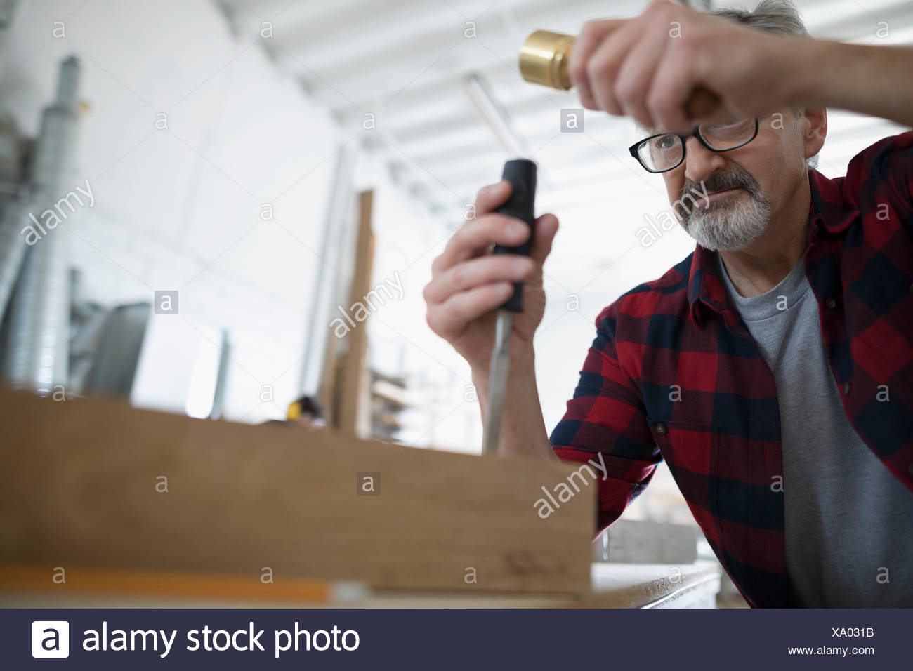 Male carpenter tapping chisel tool on wood block at workbench in workshop - Stock Image
