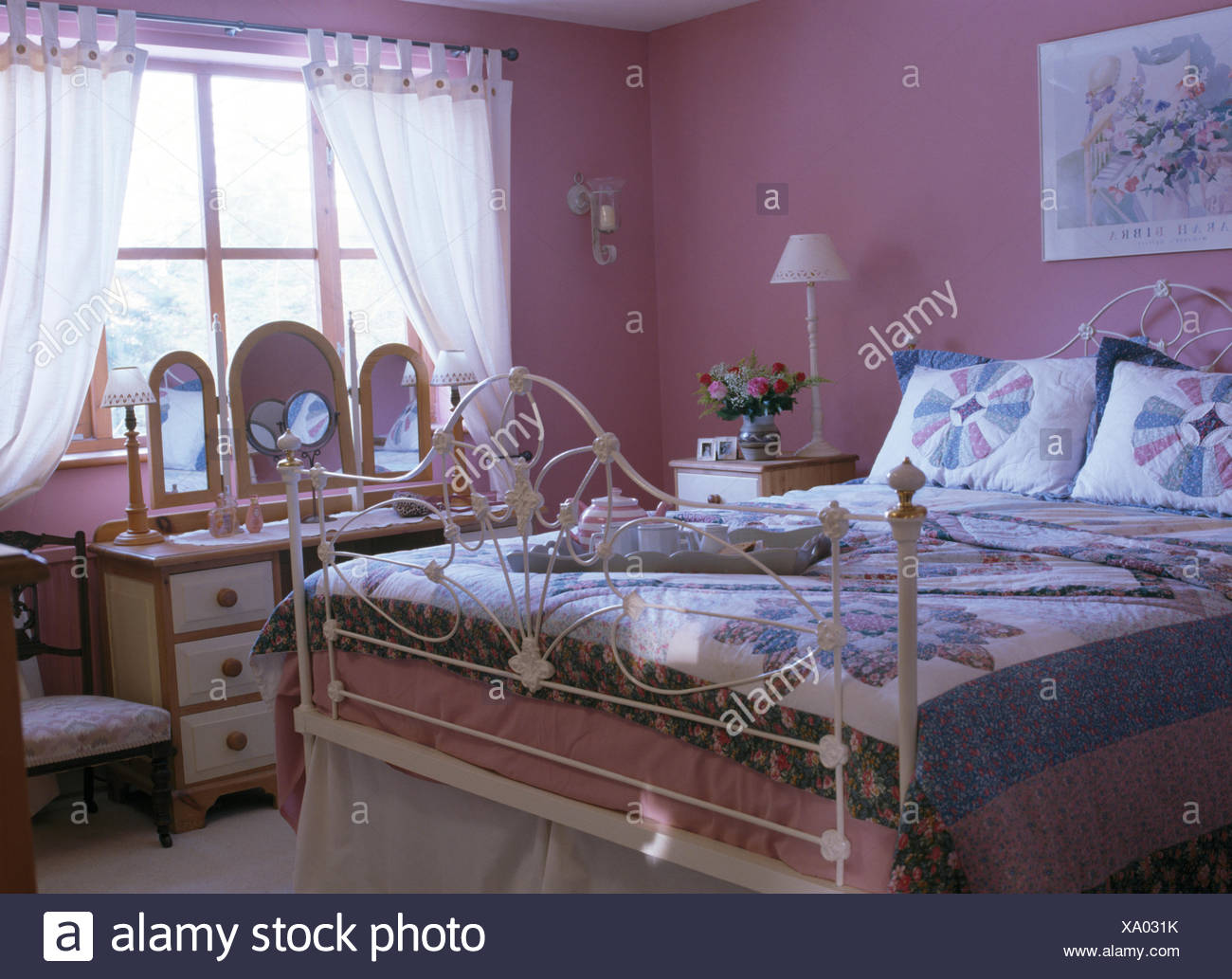 Ornate white wrought iron bed with patchwork quilt and ...