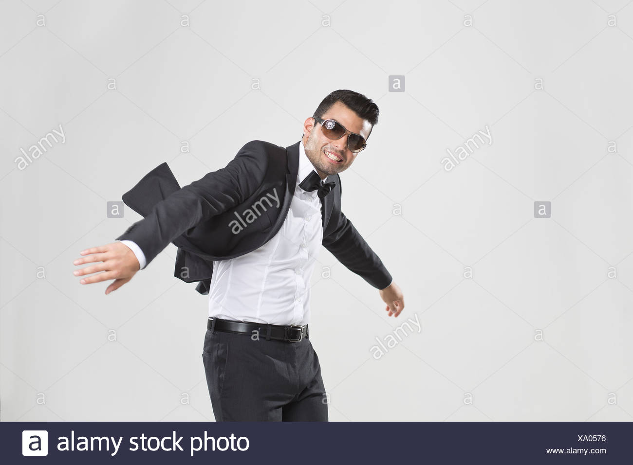Smiling man in tuxedo dancing - Stock Image
