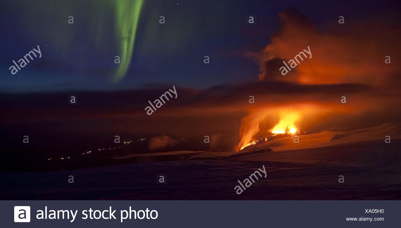 Auroras with volcano eruption in Iceland at Fimmvorduhals, a ridge between Eyjafjallajokull glacier and Myrdalsjokull Glacier. - Stock Image