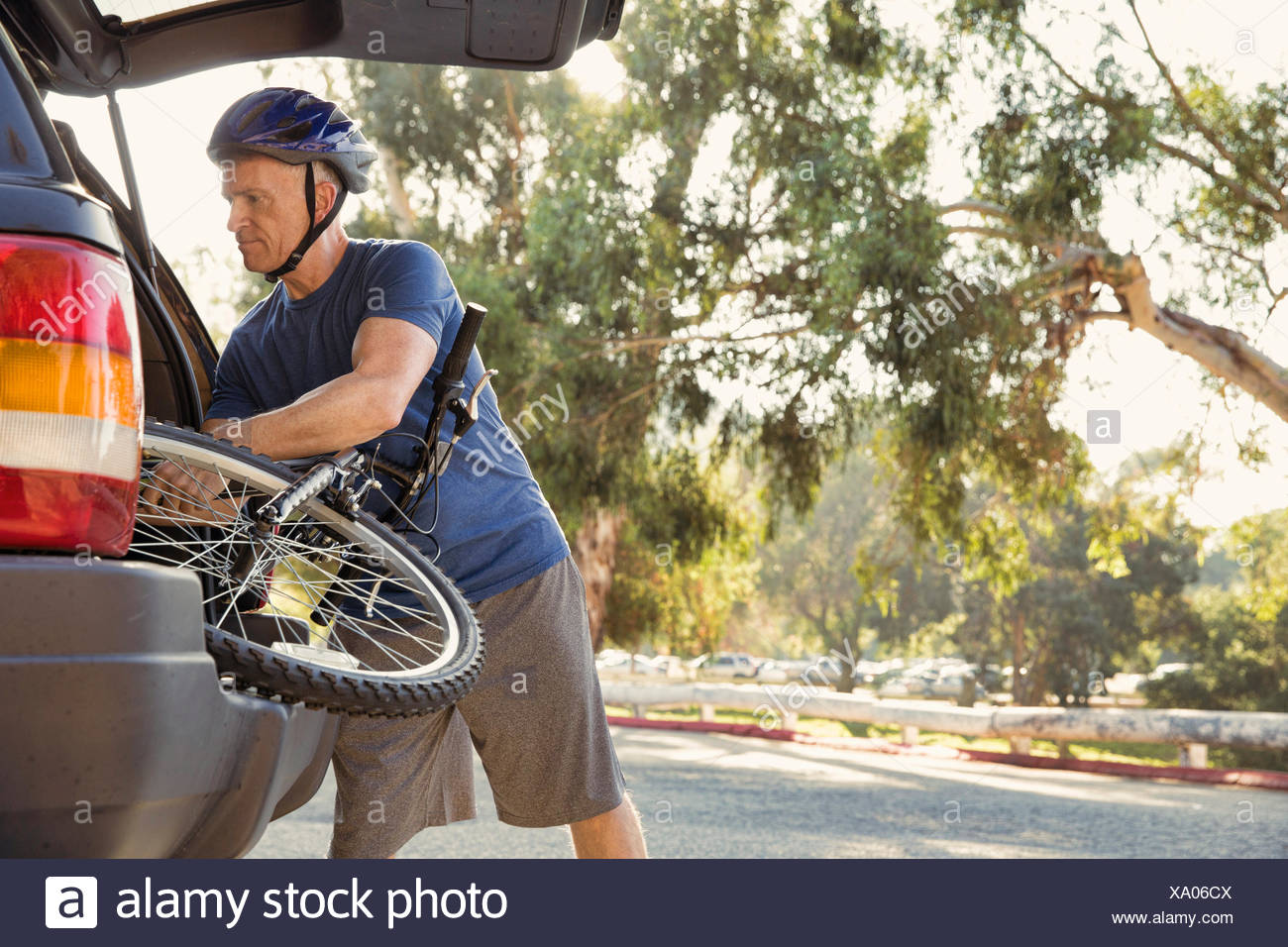 Mature man removing bicycle from car boot in park - Stock Image